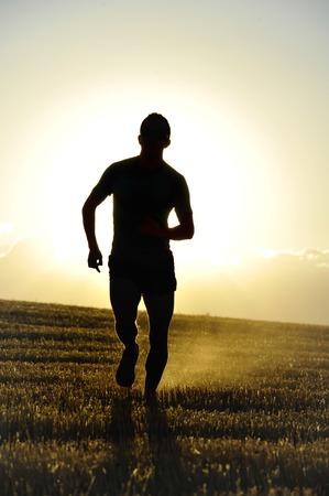 hombre deportista: silueta de hombre joven deportiva corriendo fuera de la carretera en el campo paja campo con fuerte contraluz al atardecer de verano en un hermoso paisaje rural en el estilo de vida saludable y el concepto de formación