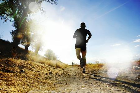 Silhouet van jonge sport man lopen op het platteland in de cross country wedstrijd in de zomer zonsondergang met agressieve hoog contrast zonlicht effect en flare in een gezonde leefstijl concept Stockfoto - 44191221