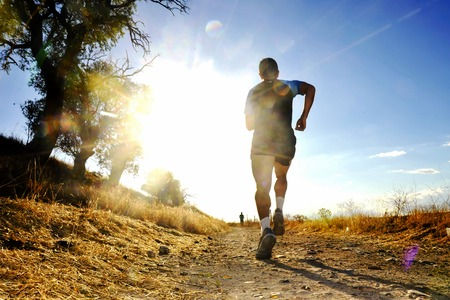 fit man: Silhouette of young sport man running on countryside in cross country competition at summer sunset with harsh high contrast sunlight effect and flare in healthy lifestyle concept Stock Photo