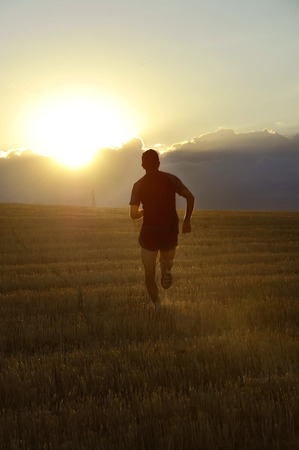 outdoor training: Silhouette of young sport man running off road in countryside on yellow grass field under summer blue sky at sunset in healthy lifestyle and training concept with high contrast and lens flare Stock Photo