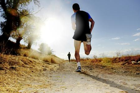 Silueta de joven deportiva que se ejecuta en campo en la competencia a campo traviesa al atardecer de verano con duras alto contraste la luz del sol efecto y los brillos en concepto de estilo de vida saludable