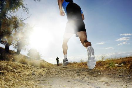 過酷な高コントラスト日光効果で夏の夕暮れ時の国競争クロスの田舎と健康的なライフ スタイルのコンセプトでフレアで走っている若いスポーツ人