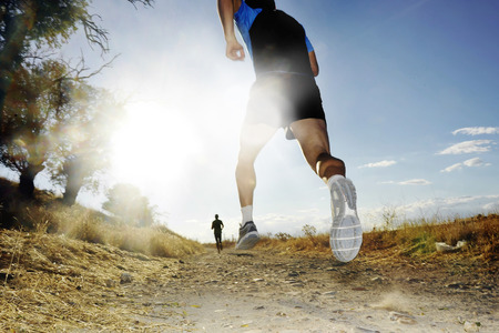 Silhouette of young sport man running on countryside in cross country competition at summer sunset with harsh high contrast sunlight effect and flare in healthy lifestyle concept 스톡 콘텐츠