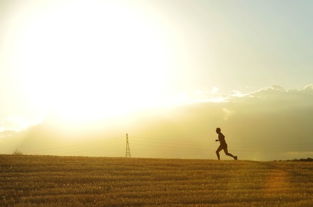 profile silhouette of young man running in countryside training cross country jogging discipline in summer sunset on beautiful rural landscape Stock Photo