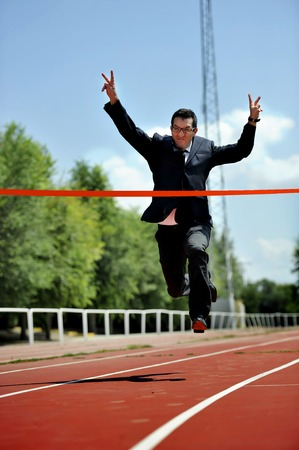 work suit: businessman running in suit and tie celebrating race victory on athletic track doing winning sign with arms in work and career success concept