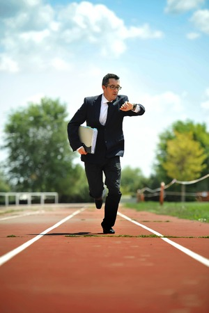 looking for work: businessman in suit and necktie carrying folder portfolio and files looking on his wrist watch watch running on athletic track in stress late for work meeting in  urgent problems concept