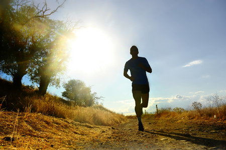 Voorzijde silhouet van jonge sport man lopen op het platteland in de cross country training in de zomer zonsondergang met harde zonlicht effect in de concurrentie opoffering en gezonde leefstijl concept Stockfoto - 44225679