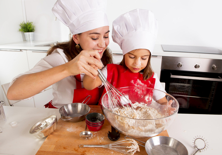 fun: happy mother baking with little daughter in apron and cook hat working with flour , bowl and spoon preparing dough teaching the kid cooking and having fun together