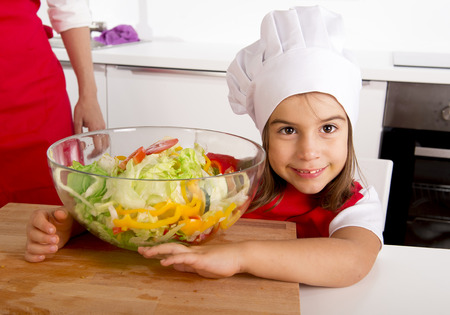 5 years old: 4 or 5 years old little girl with mother at home kitchen in red apron and cook hat holding bowl with lettuce, tomato and paprika fresh salad happy in healthy vegetable nutrition concept Stock Photo