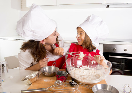 making fun: happy mother baking with little daughter in apron and cook hat working with flour , bowl and spoon preparing dough teaching the kid cooking and having fun together