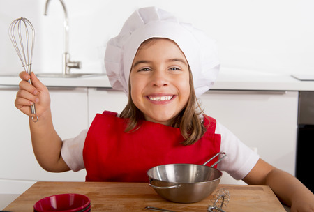 5 years old: 4 or 5 years old sweet little girl in red apron and cook hat playing chef learning cooking at home kitchen smiling happy