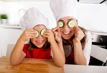 young people fun: happy mother and little daughter wearing cook hat and red apron playing with cucumber slices on the eyes at home kitchen having fun in healthy nutrition and education concept