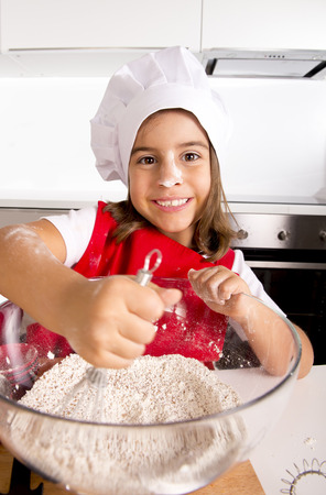 5 years old: happy little 4 or 5 years old girl learning baking mixing flour in bowl wearing red apron and cook hat smiling satisfied and proud at home kitchen in self made and education concept