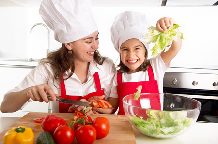 hispanic kids: young mother preparing salad for lunch wearing apron and cook hat at home kitchen with little daughter playing with lettuce and having fun together in healthy nutrition education concept