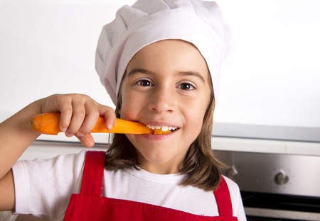 5 years old: 4 or 5 years old little girl at home kitchen in red apron and cook hat holding carrot and biting happy in healthy vegetable nutrition concept