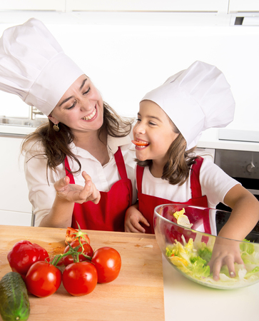 nutrition: young mother and little daughter preparing salad bow playing with tomato slice in mouth wearing apron and cook hat at home kitchen having fun together in healthy vegetable nutrition concept Stock Photo