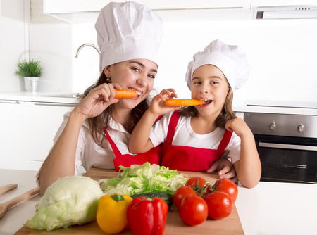kids eating healthy: happy mother and little daughter in apron and cook hat preparing salad and eating carrots together having fun at home kitchen smiling playful in healthy vegetable nutrition and education concept Stock Photo