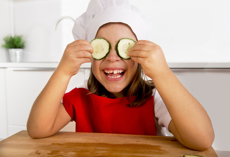 5 years old: 4 or 5 years old little girl in red apron and cook hat playing in the kitchen putting cucumber slices on her eyes smiling and laughing happy in vegetable nutrition concept