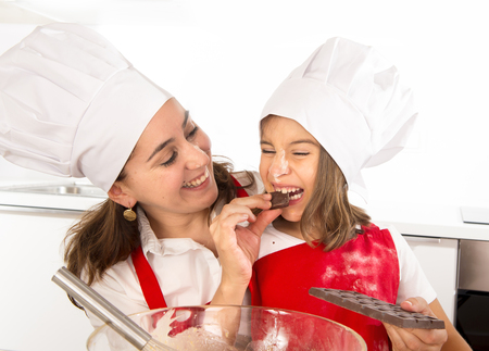 making fun: happy mother baking with little daughter eating chocolate bar used as ingredient while teaching the kid in apron and cook hat and having fun together Stock Photo