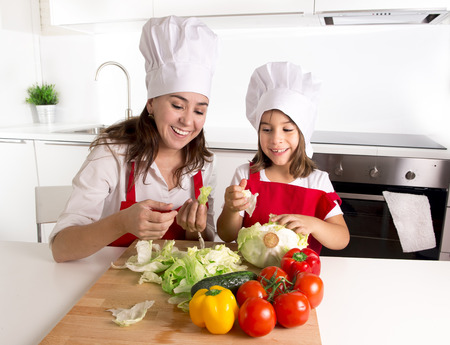 cook house: happy young mother and little daughter at house kitchen preparing lettuce and tomato salad for lunch wearing apron and cook hat having fun playing together in healthy nutrition education concept
