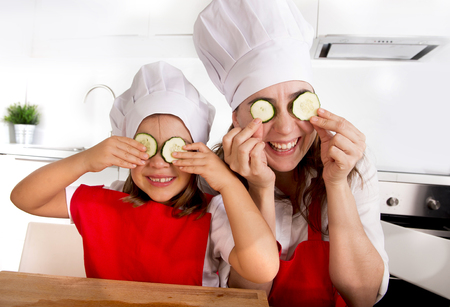 vegetable cook: happy mother and little daughter wearing cook hat and red apron playing with cucumber slices on the eyes at home kitchen having fun in healthy nutrition and education concept