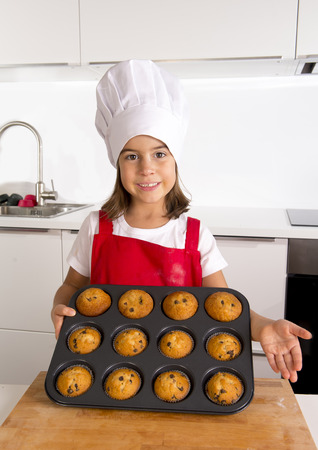 5 years old: proud female child 4 or 5 years old presenting her self made muffin cakes learning baking wearing red apron and cook hat smiling happy in bakery and cooking education  concept