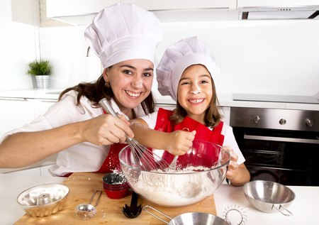 mother cooking: happy mother baking with little daughter in apron and cook hat working with flour , bowl and spoon preparing dough teaching the kid baking and having fun together Stock Photo