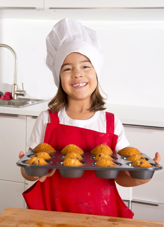 proud female child 4 or 5 years old presenting her self made muffin cakes learning baking wearing red apron and cook hat smiling happy in bakery and cooking education  concept