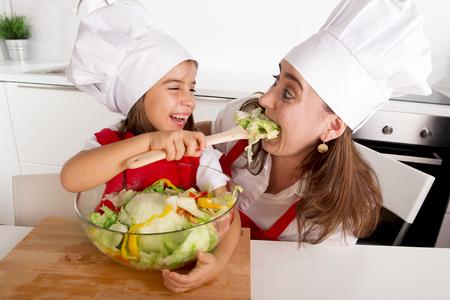 mignonne petite fille: jeune m�re et sa petite fille � la cuisine � domicile amuser et de plaisanter avec saladier portant tablier et chapeau cuire jouant ensemble dans concept de la nutrition saine �ducation l�gumes