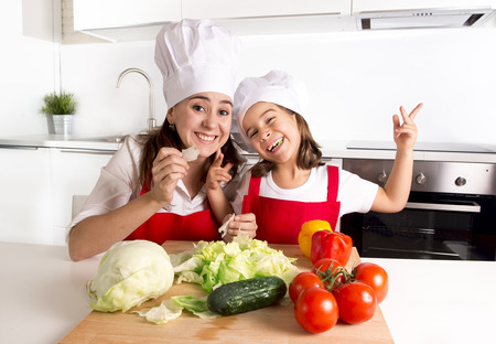 kitchen aprons: happy young mother and little daughter at house kitchen preparing lettuce and tomato salad for lunch wearing apron and cook hat having fun playing together in healthy nutrition education concept