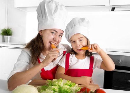 eating salad: happy mother and little daughter in apron and cook hat preparing salad and eating carrots together having fun at home kitchen smiling playful in healthy vegetable nutrition and education concept Stock Photo