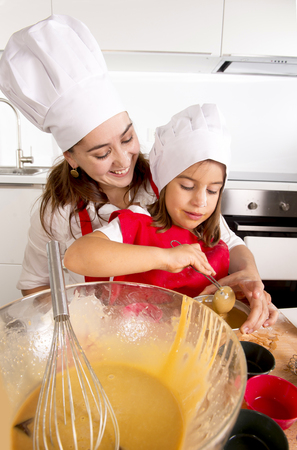 making fun: happy mother baking with little daughter in apron and cook hat filling mold muffins with dough and chocolate teaching the kid cooking and having fun together