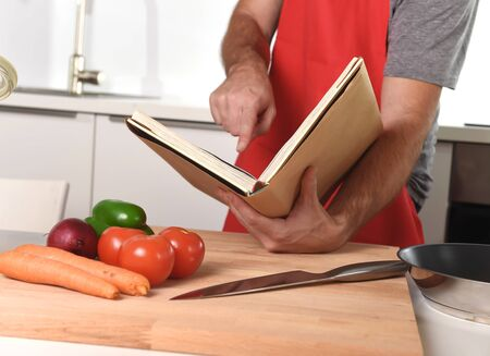 cook book: unrecognizable man in red apron at home kitchen following recipe book preparing vegetable dish in healthy cooking learning concept
