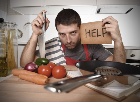 ignorant: young terrified man at home kitchen wearing cook apron showing help sign looking desperate in stress holding knife with tomato in domestic mess cooking concept