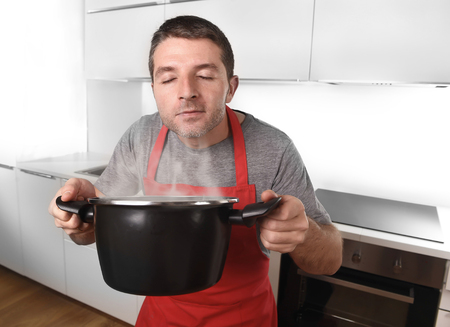 expression: young man at home kitchen in red cook apron holding pot delighted with the good smell of his dish enjoying the delicious aroma in delightful face expression