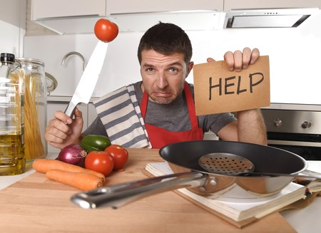 cry for help: young terrified man at home kitchen wearing cook apron showing help sign looking desperate in stress holding knife with tomato in domestic mess cooking concept
