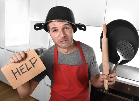 funny: funny 30s Caucasian man holding pan and household with pot on his head in red apron at home kitchen asking for help unable to cook showing panic on cooking with funny face expression Stock Photo