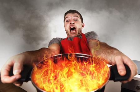 cooking eating: joven cocinero en casa sin experiencia con el delantal de la celebración de ardor olla en llamas con la cara de estrés y pánico expresión en el fuego en la cocina y cocinar concepto erróneo