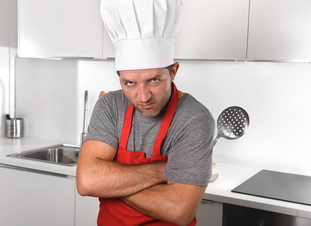 overwork: 30s attractive Caucasian man holding skimmer and rolling pin wearing red apron and cook hat at home kitchen in stress with angry upset face expression in overwork concept Stock Photo