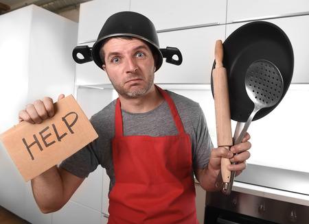 30s divertido caucásica hombre que sostiene la cacerola y hogar con el crisol en su cabeza en delantal rojo en la cocina en casa pidiendo ayuda no puede cocinar mostrando pánico en la cocina con la expresión divertida cara