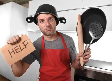 funny 30s Caucasian man holding pan and household with pot on his head in red apron at home kitchen asking for help unable to cook showing panic on cooking with funny face expression Stockfoto