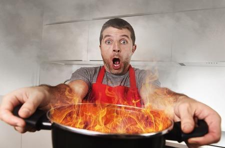ストレスとパニック顔の表情キッチンと調理の間違った概念で火の炎で燃えてポットを保持しているエプロンの若い経験の浅い家庭料理