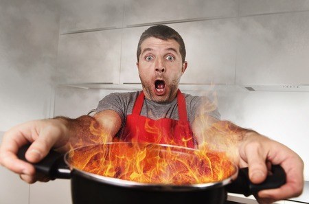 terrorized: young inexperienced home cook with apron holding pot burning in flames with stress and panic face expression in fire in the kitchen and cooking wrong concept
