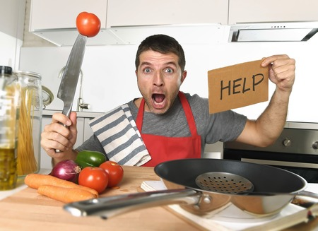 mess: young terrified man at home kitchen wearing cook apron showing help sign looking desperate in stress holding knife with tomato in domestic mess cooking concept