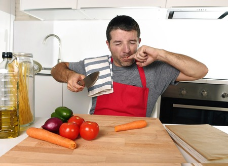 fingers: young attractive home cook man in red apron slicing carrot with kitchen knife  suffering domestic accident cutting and hurting his finger while cooking in pain face expression Stock Photo