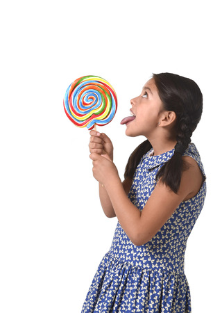 lolli: happy female child holding big lollipop candy licking the candy with her tongue in sugar addiction and kid love for sweet concept isolated on white background
