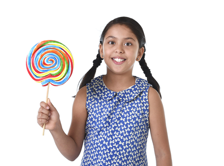 lolli: Latin female child holding huge lollipop happy and excited wearing cute blue dress and pony tails standing isolated on white background in kid loving candy and sweet sugary food concept