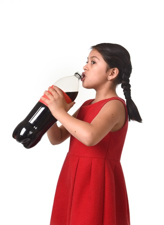 soda bottle: happy female child holding big cola soda bottle drinking isolated on white background in sugar drink abuse and addiction and sweet nutrition excess Stock Photo