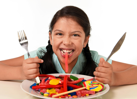young: happy excited Latin female child holding fork and knife sitting at table ready biting candy from a  dish full of  lollipop and sugary things in unhealthy sweet nutrition and kid in sugar abuse concept