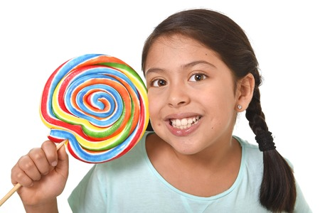 lolli: happy female hispanic child holding big lollipop candy in cheerful face expression in sugar addiction and kid love for sweet concept isolated on white background